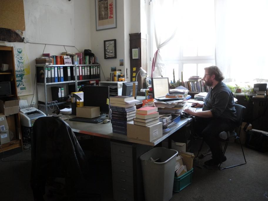 Der Verleger in seinem Büro bei der Arbeit.