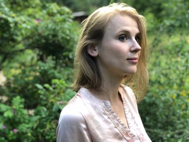 Marie Franz steht im Garten, sie guckt nach rechts aus dem Bild.