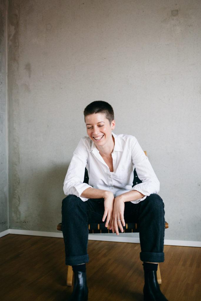 Emilia von Senger sitzt vor einer weißen Wand
