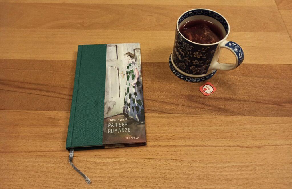 """Franz Hessels Buch """"Pariser Romanze"""" liegt auf einem Holztisch. Rechts daneben eine blau-weiße Tasse Tee."""